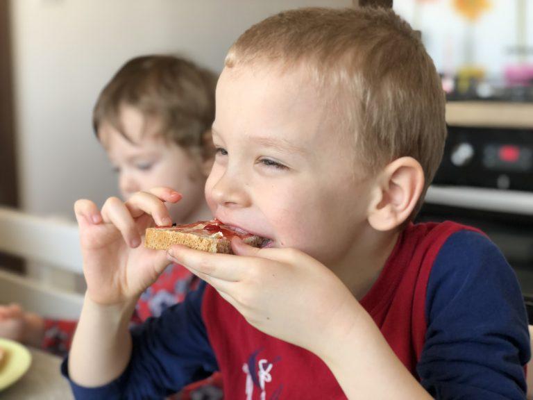 Little boy eating homemade sourdough bread with jam