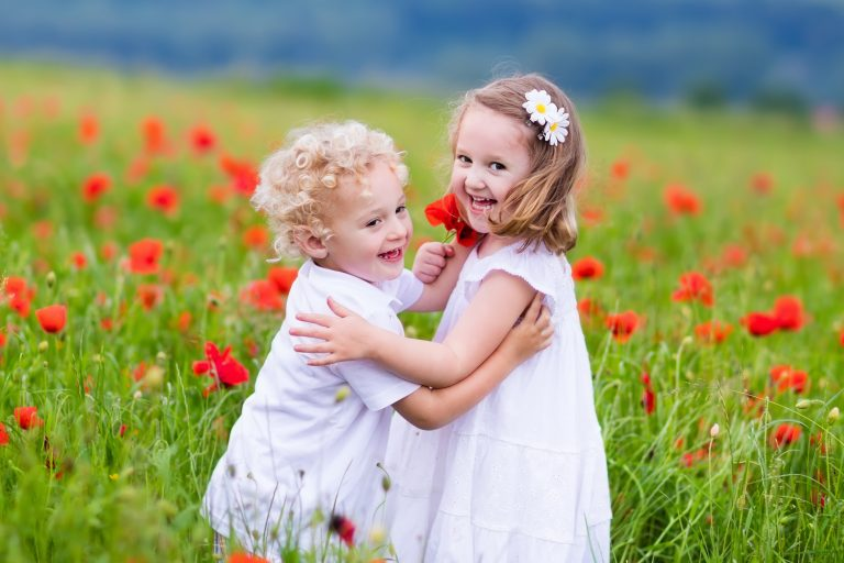 siblings with poppy flowers