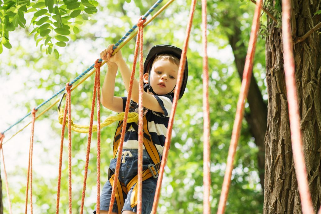 kid playing in the ropes in adventure park